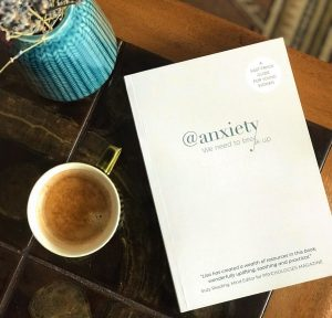 anxiety book on a table with a cup of coffee